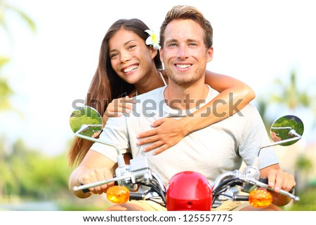Happy young couple in love on scooter driving together. Multiracial couple having fun in the free outdoor. Smiling Caucasian man and Asian woman.