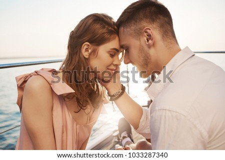 Happy young couple in love smiling and enjoying boat trip on the sea. Romance and vacation concept. Boyfriend tenderly touches her cheek and girlfriend feels butterflies in stomach #1033287340
