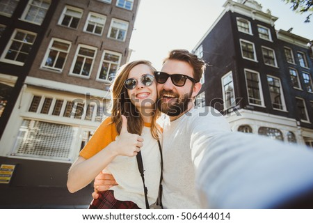 Happy young couple in love takes selfie portrait near canals in Amsterdam, Netherlands. Pretty tourists make funny photos for travel blog in Europe.
