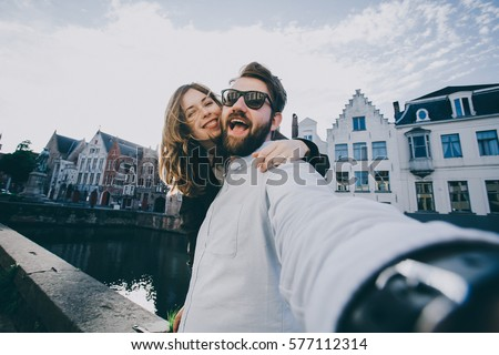 Happy young couple in love takes selfie portrait on the main street of Brugge or Bruges, Belgium. Pretty tourists make funny photos for travel blog in Europe.