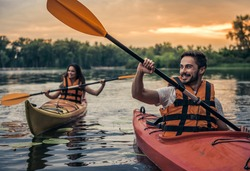 Happy young couple in sea vests is smiling while sailing kayaks