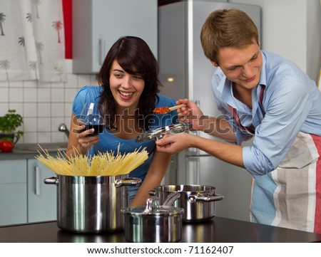 Happy young couple in the kitchen cooking dinner