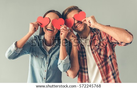 Happy young couple is holding red paper hearts and smiling, on gray background