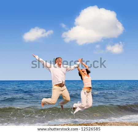 happy young couple is jumping in the beach