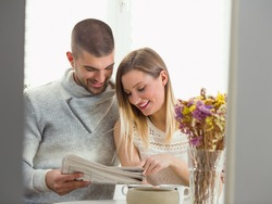 Happy young couple is spending morning together reading news. Young mixed-raced man is sitting at the dining table with his beautiful blond girlfriend, having a breakfast and reading the newspaper.