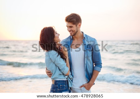 Happy young couple laughing and hugging on the beach