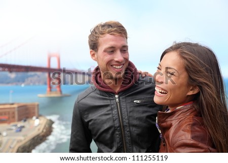 Happy young couple laughing in San Francisco by Golden Gate Bridge. Interracial young modern couple, Asian woman, Caucasian man.