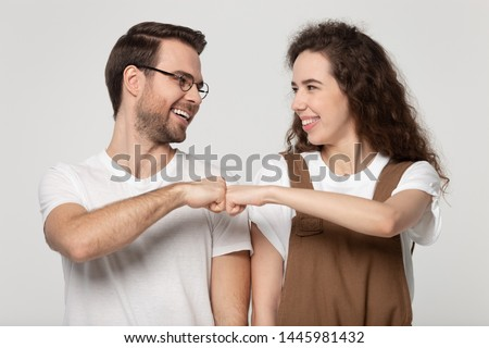 Happy young couple looking greeting each other giving fist bump hands gesture celebrating successfully passed exam or common success, like-minded people showing respect, solidarity, friendship concept