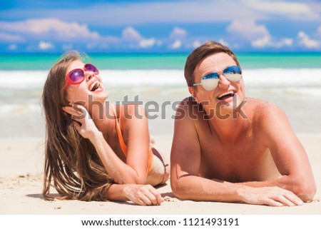 happy young couple lying and having fun on a tropical beach #1121493191