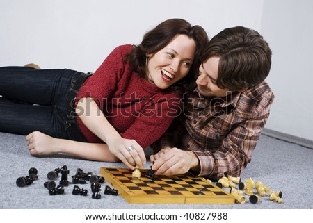 Happy young couple lying on carpet, playing chess.