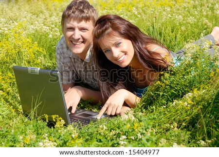 Happy young couple lying with a laptop on a wild meadow.