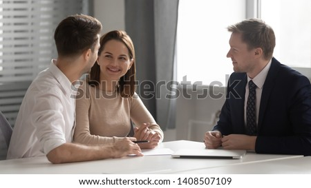 Happy young couple making decision meeting bank manager insurer, male realtor broker consulting smiling family clients offering contract, customers consider insurance loan mortgage real estate deal