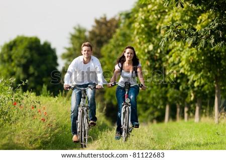 Happy young couple - man and woman - cycling in summer in nature