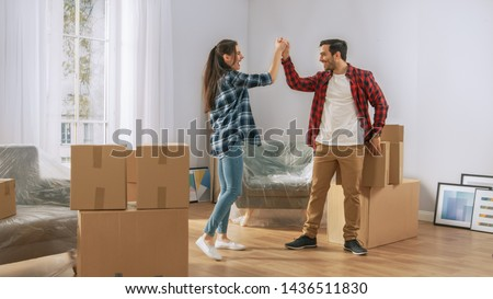 Happy Young Couple Moving in Into New Apartment, Carrying Cardboard Boxes with Stuff, Having Fun, Give High Five. Young Boyfriend and Girlfriend Start Living Together, Unpacking Stuff.