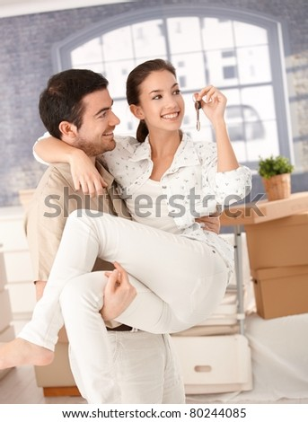 Happy young couple moving to new home, smiling, holding keys in hand.?