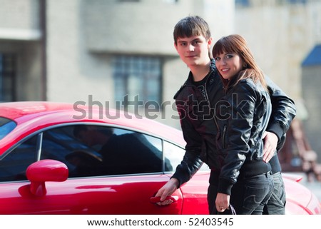 Happy young couple near the their car.