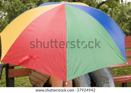 Happy young couple on a bench. Under a colorful umbrella in a privacy