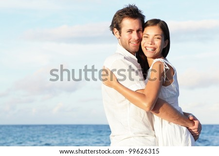 Happy young couple on beach in love embracing and hugging smiling joyful. Interracial young couple, Asian woman, Caucasian man.