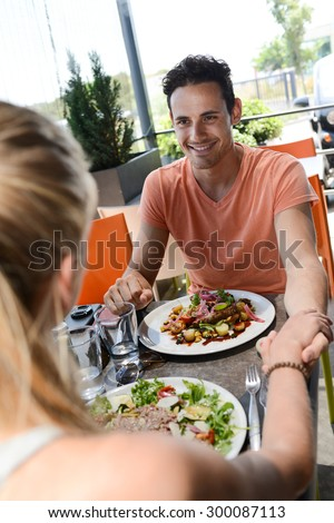 happy young couple on holiday having lunch in a restaurant terrace outdoor during summer