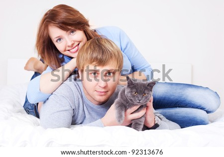happy young couple on the bed at home with their cat (focus on the  man)