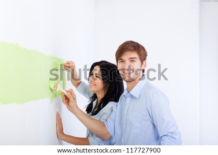 happy young couple paint in green color white wall of their new apartment home