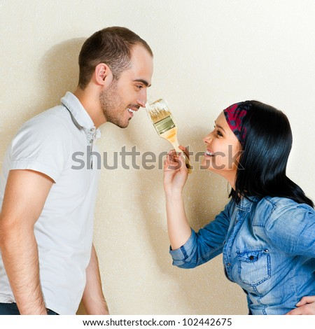 Happy young couple painting their house