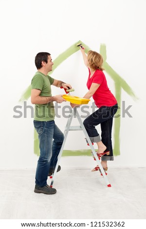 Happy young couple painting their new conceptual home - stock photo