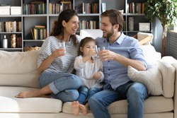 Happy young couple parents teaching little preschool daughter drinking clear water every day. Smiling healthy family holding glasses with pure aqua, enjoying morning daily healthcare habit at home.