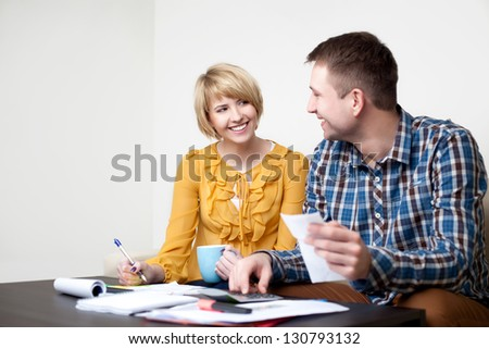 Happy young couple paying bills at home.