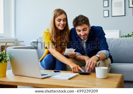 Happy young couple paying bills together and managing budget, sitting on the sofa and using calculator and laptop