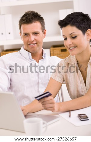 Happy young couple paying with credit card at home.