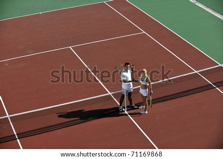 happy young couple play tennis game outdoor man and woman
