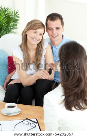 Happy young couple receiving their new car's key sitting on a sofa