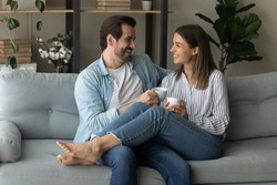 Happy young couple relaxing on cozy couch at home, holding cups, drinking hot beverages, tea or coffee together, laughing man and woman enjoying leisure time, chatting, sharing news, having fun