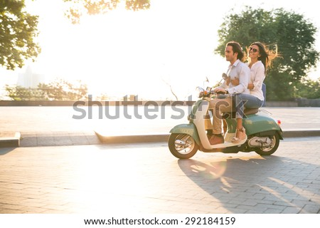 Happy young couple riding a scooter and having fun. Sun is shining in the morning