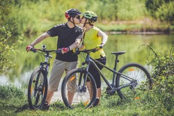 Happy young couple riding bicycles outdoors