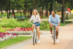 happy young couple riding bicycles together in park