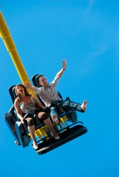 Happy young couple riding in the amusement park