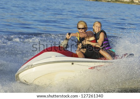 Happy young couple riding jet ski on lake