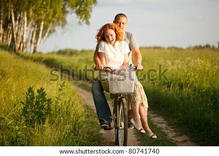 Happy young couple riding on a bicycle