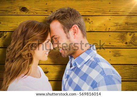 Happy young couple rubbing nose against green paint splashed surface #569816014