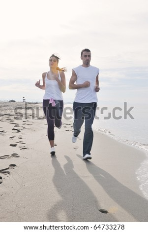 happy young couple running and jogging on beach at early morning