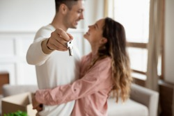 Happy young couple show new own house keys excited to move together, smiling loving millennial husband and wife overjoyed first time buyers relocate rent shared apartment, ownership concept