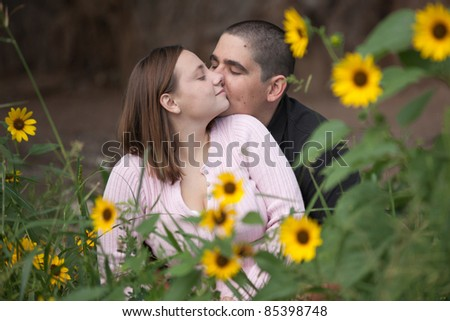 Happy young couple showing affection towards each other, while sitting in a field of flowers outdoors