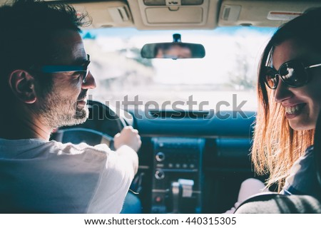 Happy young couple sit in a car. Travel and adventure concept. Toned picture