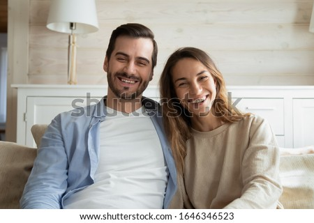 Happy young couple sit on couch in living room look at camera talk on video call at home, smiling millennial man and woman having webcam conversation using unlimited internet connection