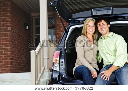 Happy young couple sitting at back of car on driveway