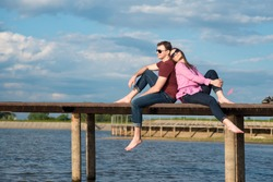 Happy young couple sitting back to back on the pier in the sunny day