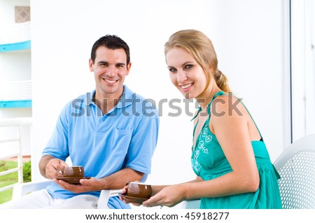 happy young couple sitting on balcony drinking coffee
