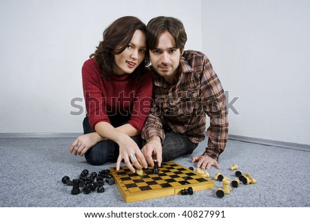 Happy young couple sitting on carpet, playing chess.